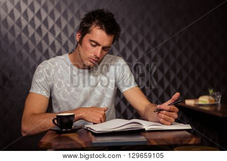Hipster having coffee and writing in planner in coffee shop