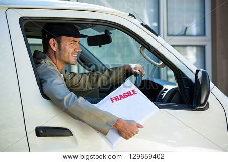 Delivery man with fragile parcel looking through van window