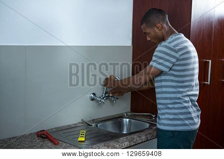 Plumber fixing the sink in kitchen