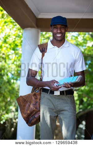 Portrait of happy postman delivering letter