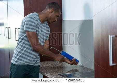 Man using pest control injection in kitchen
