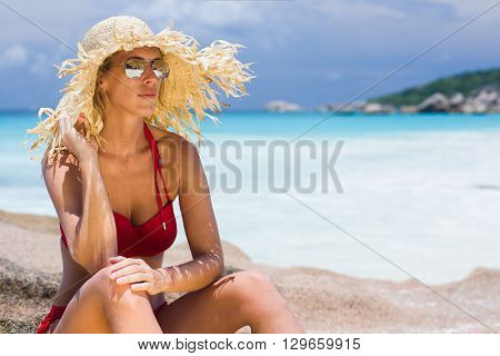 Beautiful blonde woman with straw sunhat and sunglasses, tropical environment