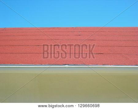 a picture of an exterior 1870's adobe building refurbished red  shingle roof