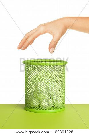 hand near wastebasket full of waste paper and fly ball