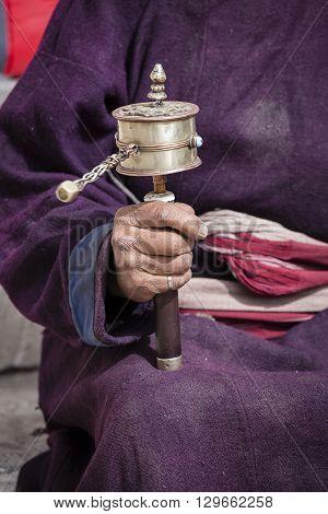 Old Tibetan woman holding buddhist prayer wheel in Lamayuru Gompa Ladakh India. Hand and prayer wheel close up