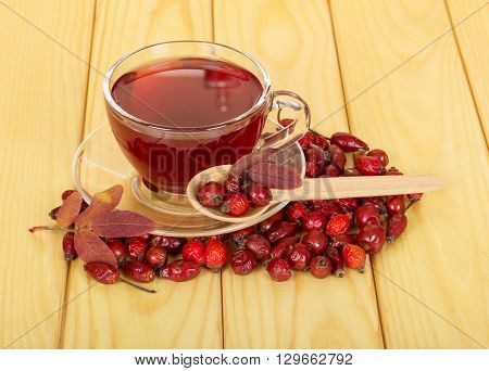 Glass Cup with rose hips on wooden background closeup