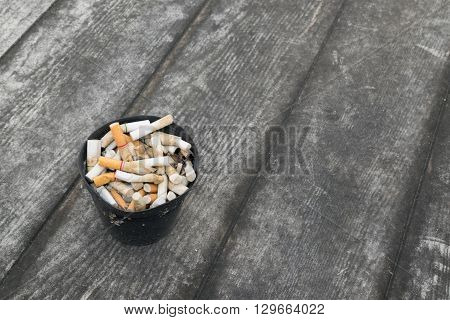 Cigarette in outdoors ashtray with sand on wooden floor