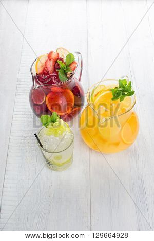 The two pitchers of lemonade, berry fruit drink and a glass of water with lemonade and grapes on a white wooden background, top view