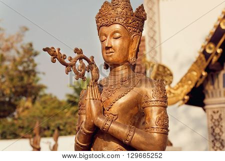Calmness Buddha with crown. Sculpture of praying Buddha at the entrance of a traditional Thai temple