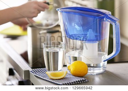 Water filter jug with lemon and glass on kitchen table