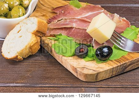 Refreshments of sliced Spanish ham green and black olives bread and arugula. Everything is lying on a wooden table and in a white bowl. The piece of cheese is impaled on a fork. Horizontally.
