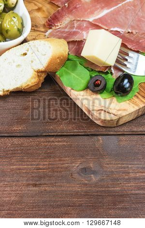 Refreshments of sliced Spanish ham green and black olives bread and arugula. Everything is lying on a wooden table and in a white bowl. The piece of cheese is impaled on a fork.Vertically.