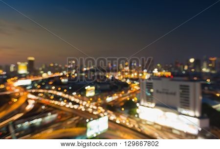 Aerial view night view, blurred bokeh lights, city downtown and highway interchanged