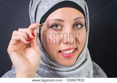 Beautiful muslim woman plucking her eyebrows alone