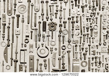 set of old rusty metal screws nuts and bolts on a gray background. black and white photo. Flat lay top view