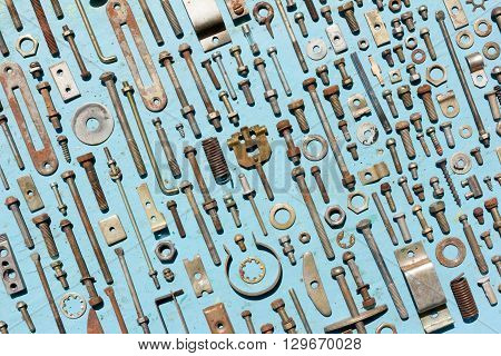 set of old rusty metal screws nuts and bolts on a blue background. Flat lay top view