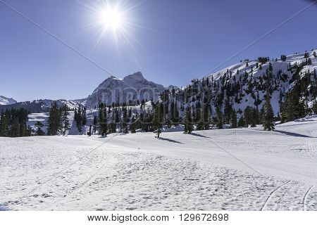 Bright sun starbust over Mt Shuksan in Cascade range