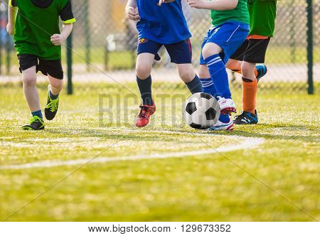 Kids play soccer football game. Boys playing soccer match on a sports venue