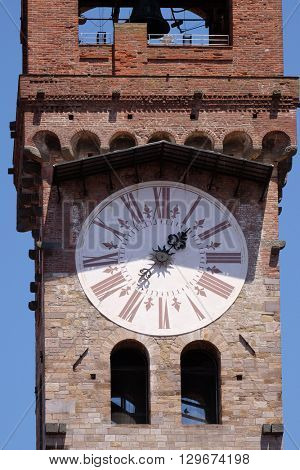 LUCCA, ITALY - JUNE 06, 2015: Torre dell'Orologio, Stone Bell Tower (Campanile) topped with brick arch and clock with roman numerals in Lucca, Italy, on June 06, 2015