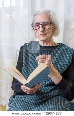 Grandma Reading A Book Through Magnifying Glass