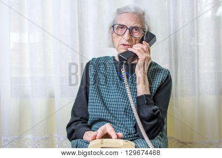 Elderly Woman Using The Phone Indoors
