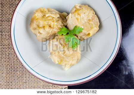 Chinese yum cha pork dumpling Shumai in white bowl.