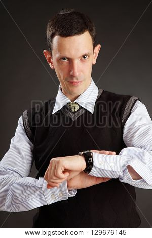 Businessman is  looking on his watch over dark grey background