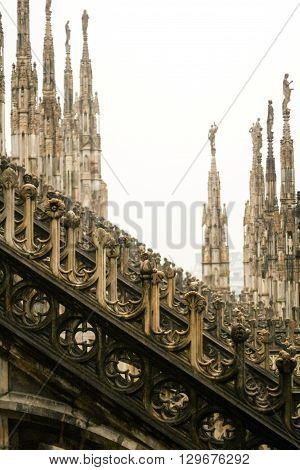 The roof of the Duomo - the cathedral of Milan. Superb gothic architecture of limestone