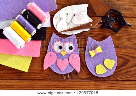 Set for sewing a felt owl, paper templates, felt sheets, scissors, thread, needle, pins on a brown wooden background