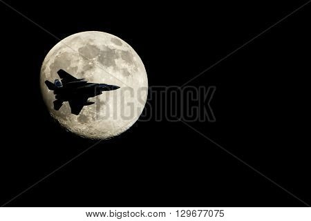 Silhouette of airplane flying in front of moon.