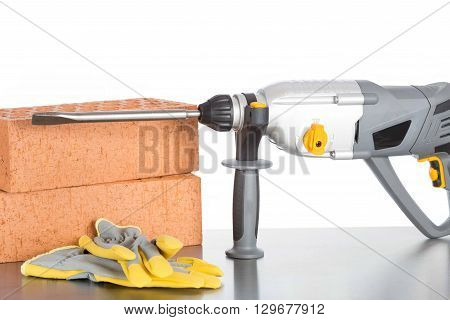 Hammer with bricks and protective a gloves