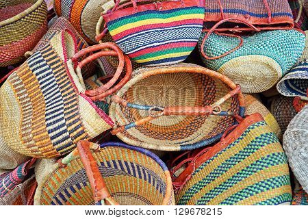 Colorful wicker (or straw) bags jumbled in a pile.