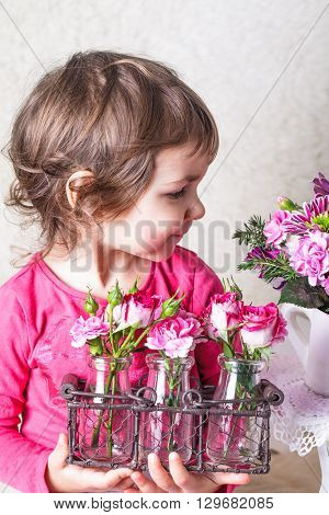 Little girl is smelling the roses. Close up face