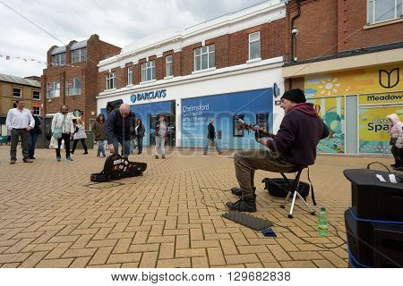 Street Busker Entertaining Crowds Of Shoppers