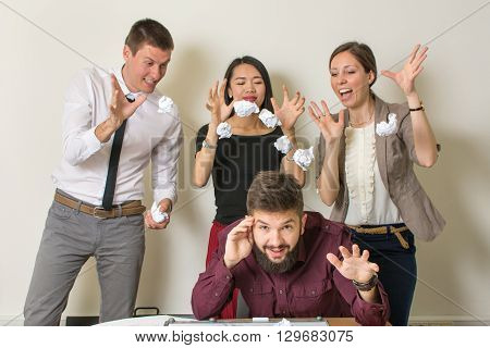 People throwing papers on a colleague at the office