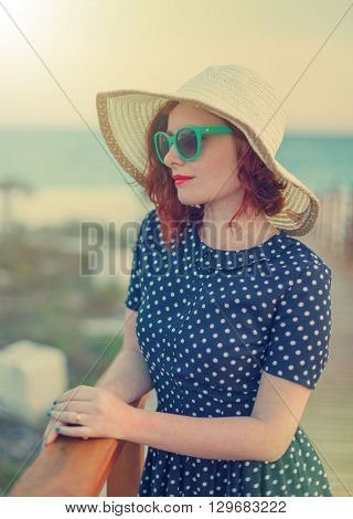 Red-haired girl in a hat and sunglasses on the background of the sea