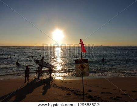WAIKIKI - JANUARY 10: People watch dramatic Sunset dropping behind the ocean on Kaimana Beach over the water with strong current sign on Oahu Hawaii on JANUARY 10 2016.