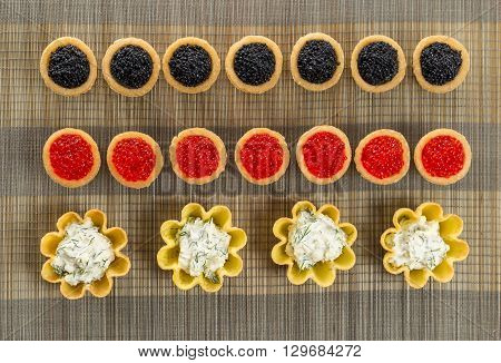 Tartlets filled with cheese and dill salad and caviar on bamboo placemat horizontal top view