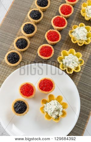 Tartlets filled with cheese and dill salad and caviar on bamboo placemat and plate with tartlets overhead view
