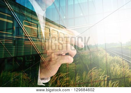 Double Exposure of Businessman writing Glass decorated Building and Train on Rural Scene with sunrise as Conceptual image
