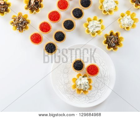 Tartlets filled with cheese and dill salad and caviar and plate with tartlets against white background close up horizontal top view
