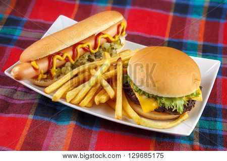 Hot dog with french fries and cheese burger on plate fast food lunch on red fabric surface