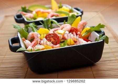 Fresh salad avocado shrmips and mango on table matt