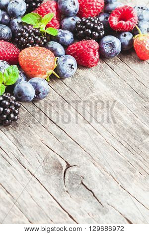 Summer wild berries over shabby wooden  background. Raspberry, strawberry, blackberry and blueberry on the table