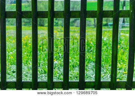 Detail of railing with grass field behind it. Old wooden railing protecting garden