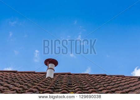 Chimney on a cabin roof with sky almost without clouds.
