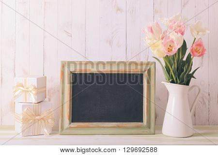 Pink tulips in jug and green wooden chalkboard. Teacher's day concept