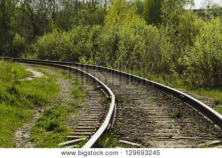 Railroad tracks on the background of green bushes bright sunny day