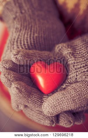 Close-up of hands in grey knitted mittens holding red heart