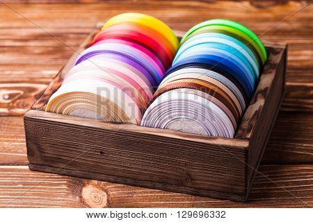 Various colors ribbon bobbins in vintage wooden box